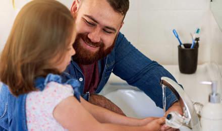 Isä auttaa tytärtään pesemään kädet juoksevan veden alla