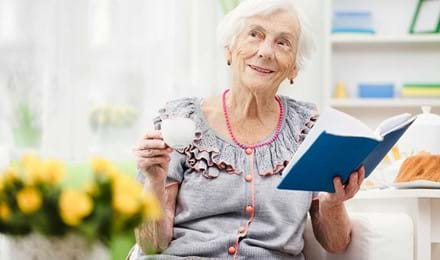Iäkäs nainen istuu sohvalla pidellen kirjaa ja teekuppia