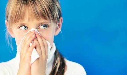 Flunssainen tyttö pitelee paperinenäliinaa nenänsä edessä
