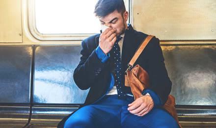 Pukumies istuu junassa ja niistää nenäänsä