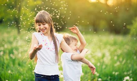 Veli ja sisko leikkivät voikukkaniityllä siitepölyn keskellä