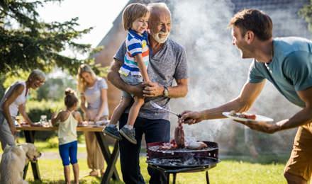 Mies valmistelee grillijuhlia perheen takapihalla