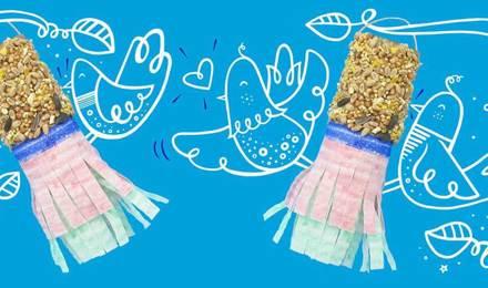 Itsetehdyt lintulaudat, joilla on siemeniä ja koristepaperia, riippumassa piirretyiltä puunoksilta sekä piirrettyjä lintuja