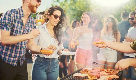 Kaveriryhmiä grillijuhlissa grillin ympärillä