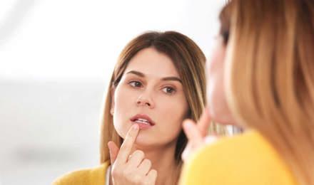 Femme traite un bouton de fièvre devant le miroir