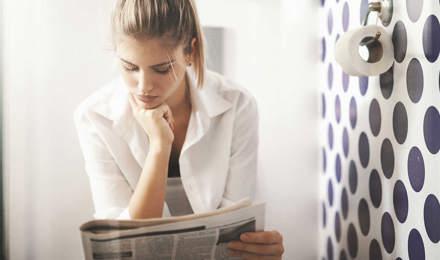 Une femme qui lit le journal aux toilettes