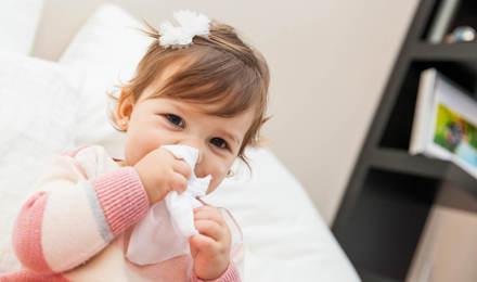 Une petite fille essuie son nez avec un mouchoir