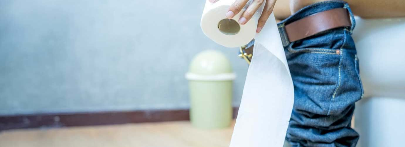Femme dans les toilettes qui montre comment utiliser moins de papier toilette