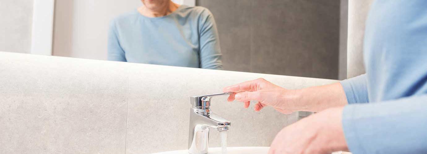 Une femme âgée utilise le robinet  pour nettoyer sa brosse à dents