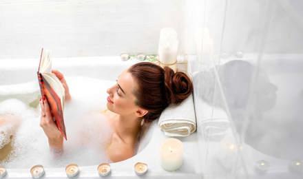 Une femme lit dans un bain à bulles avec des bougies allumées