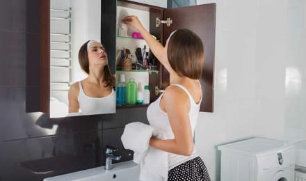 Femme qui utilise des conseils d'organisation de la salle de bain pour ranger les placards