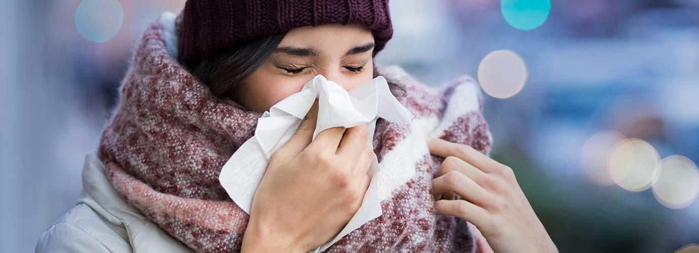 Paksuihin talvivaatteisiin sonnustautunut nainen kärsii poskiontelotulehduksen oireista ja aivastaa nenäliinaan ulkona