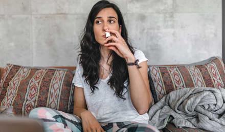 Koivun siitepölyallergiasta kärsivä nuori nainen istuu sohvalla pidellen nenäsumutetta nenäänsä vasten