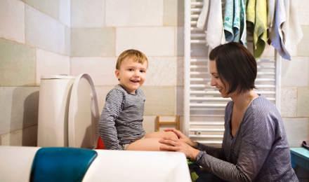 Äiti auttaa poikaansa istumaan vessassa potalla