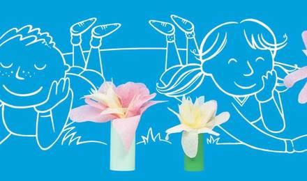 Piirretyt lapset ihastelevat askarreltuja kukkia opittuaan ensin itse valmistamaan paperikukkia kartonkiputkista ja paperista