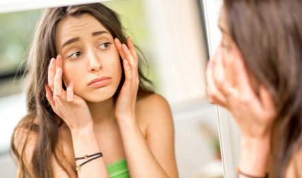 Un adolescent vérifie ses yeux gonflés par les allergies dans le miroir