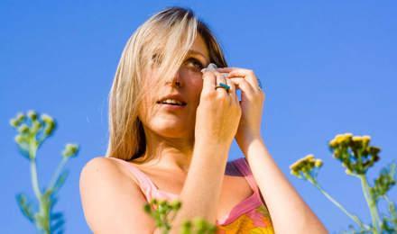 Une femme au milieu des fleurs avec une allergie au pollen