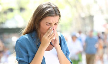 Femme avec rhume en été se mouchant