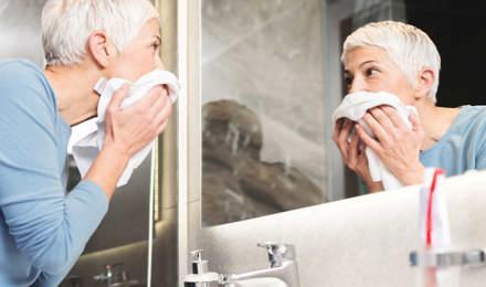 Une femme avec des  cheveux blancs et courts regarde dans le miroir de salle de bain après avoir rincé son visage pour soulager ses yeux larmoyants à cause de l'allergies