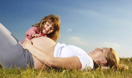 Une mère enceinte et son jeune enfant assis dans un champ avec un ciel bleu semble avoir besoin de soulager son rhume des foins pendant la grossesse.