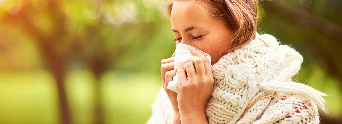 Une jeune femme éternue dans un parc et s'interroge sur les causes du rhume des foins