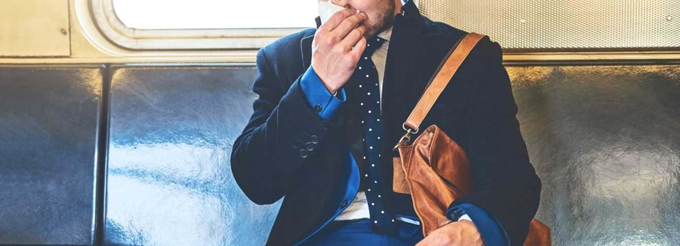Un homme vêtu d'un costume se mouche assis dans un wagon de train