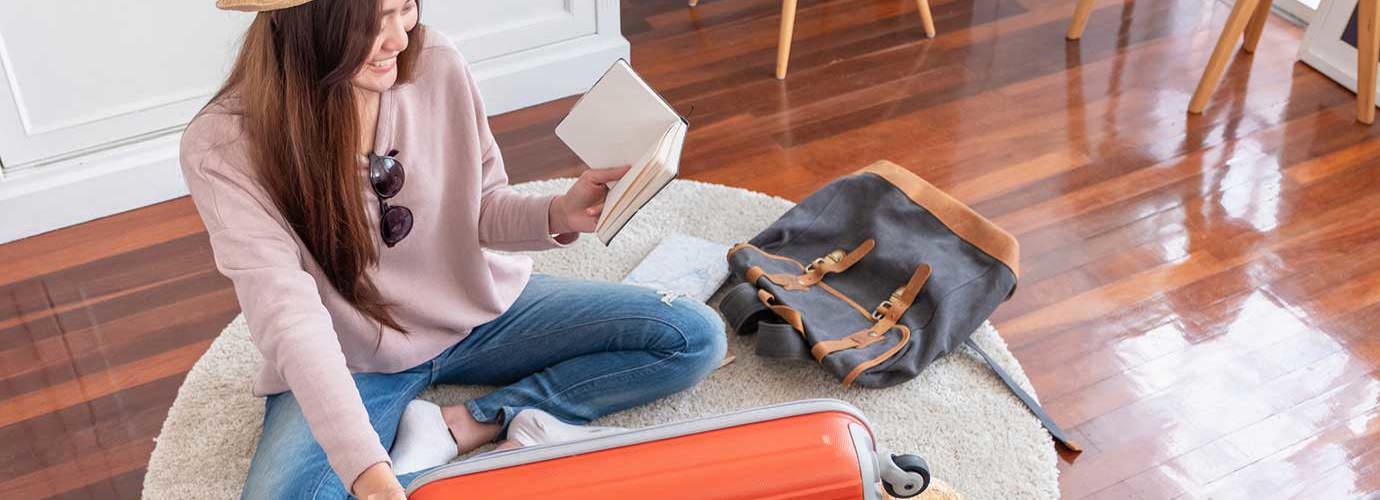 Une jeune femme assise sur le plancher prépare sa valise pour les vacances d'été