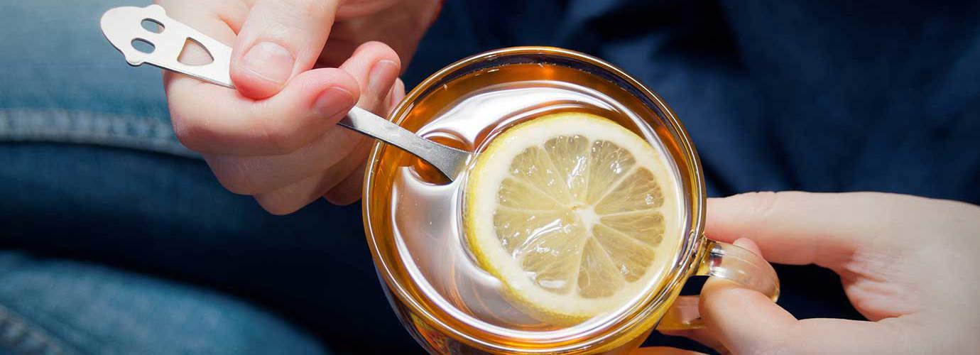 Une personne tient une tasse en verre remplie d'eau chaude avec du miel et du citron