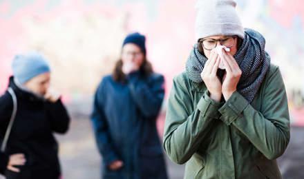 Une jeune femme qui éternue  peut vouloir des remèdes maison contre le nez bouché