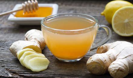 Du gingembre entier et haché, du miel, du citron et un verre de mélange sur une table en bois
