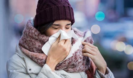Femme enveloppée dans de gros vêtements d'hiver et qui souffre des symptômes de la sinusite,  elle éternue dans un mouchoir