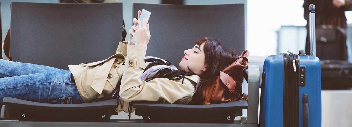Une femme installée sur plusieurs sièges dans un aéroport lit un livre avec une valise à roulettes à côté d'elle