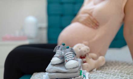 Un tas soigné de vêtements de bébé sur un lit avec une femme enceinte assise en arrière-plan