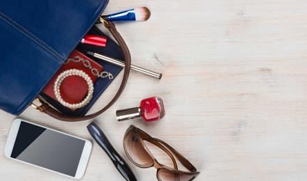 Le sac d'une femme sur un bureau en bois avec son contenu qui déborde
