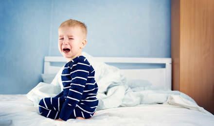 Un jeune enfant pleure assis sur un lit