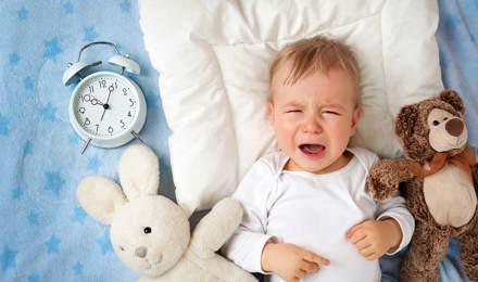 Un bébé pleure sur une couverture entourée de deux jouets en peluche et d'un réveil analogique