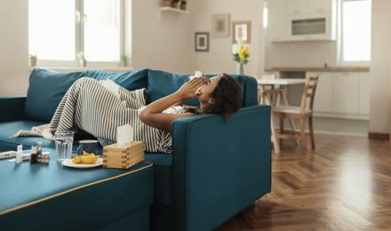 Nainen, jolla on ärsyttävä yskä, yrittää juoda teetä