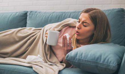Une femme tousse couchée dans canapé tout en tenant une tasse de thé et un mouchoir