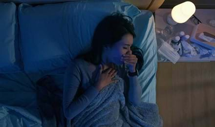 Une femme au lit tousse la nuit, il y a des médicaments sur la table de chevet