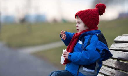 Une enfant éternue sur un banc dans un parc en hiver