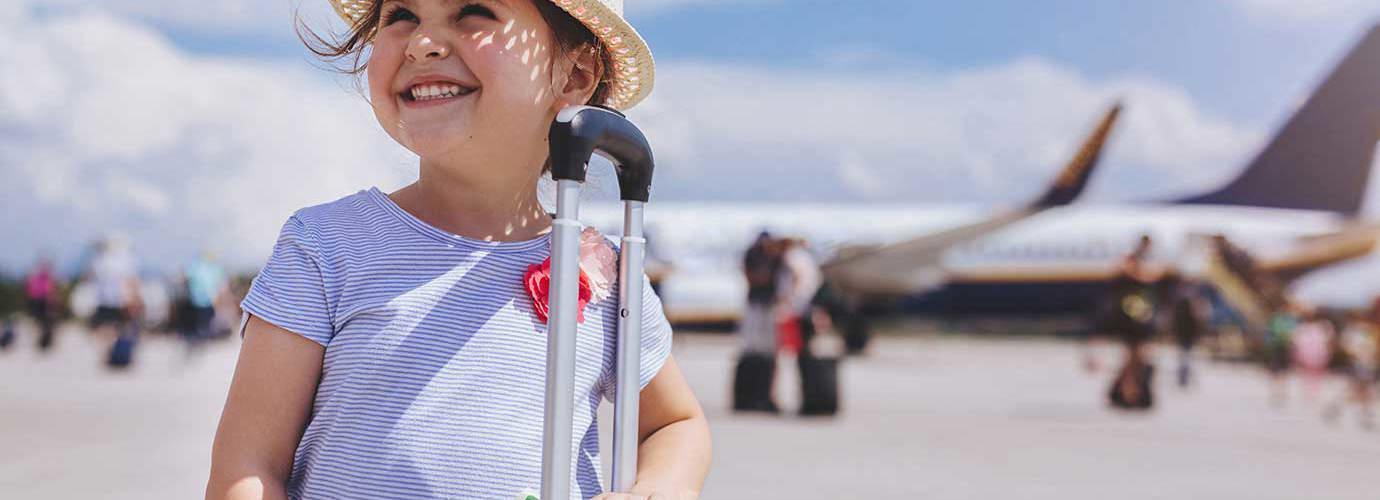 Une jeune fille souriante avec en arrière-plan une valise jaune avec des articles dont vous avez besoin pour des vacances en famille