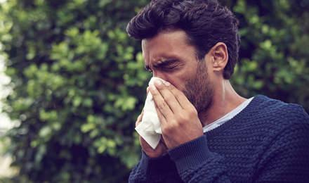 Un homme se mouche avec un mouchoir tout en ayant les  yeux larmoyants et le nez qui coule