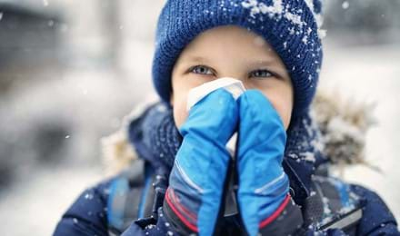 Un petit enfant vêtu de vêtements d'hiver se mouche le nez