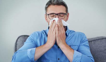 Un homme qui porte des lunettes et une chemise bleue est assis sur un canapé et se mouche le nez