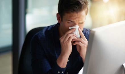 Un homme éternue vers son ordinateur, il est à la recherche de la période d'incubation du rhume