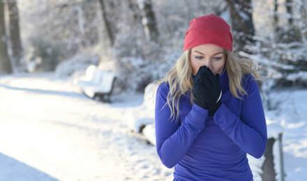 Une jeune femme court dans la neige avec un rhume et veut savoir comment traiter une allergie au pollen avec un remède maison