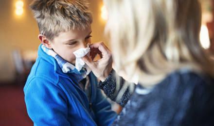 Une mère mouche le nez de son enfant et peut se demander ce qu'il faut faire pour éviter la propagation du rhume