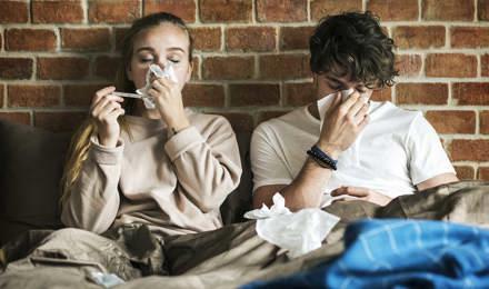 Deux jeunes adultes sont assis sous des couvertures et éternuent dans des mouchoirs avec un mur de briques derrière eux