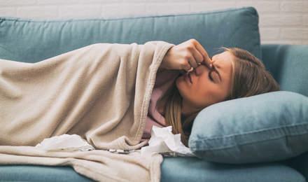 Une femme couchée dans un canapé bleu a des douleurs des sinus
