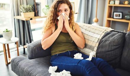 Une femme avec des symptômes de rhume des foins se mouche le nez